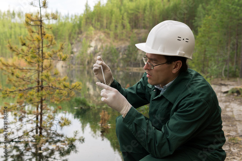 Valokuvatapetti industrial ecologist takes a sample of water from a flooded quarry