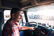 canvas print picture - Professional middle aged truck driver in casual clothes driving truck vehicle going for a long transportation route.