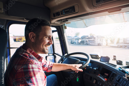 Professional middle aged truck driver in casual clothes driving truck vehicle going for a long transportation route.