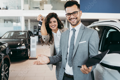 Happy and beautiful middle age business woman buying new car at showroom. A nice seller helps her make the right decision.