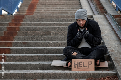 A man, homeless, a person asks for alms on the street with a Help sign Canvas Print