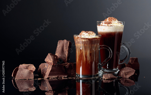 Foto op Plexiglas Chocolade Hot chocolate with whipped cream and pieces of dark chocolate on a black background.