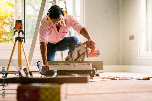 Obraz smart indian contractor hand use sawing machine wood work house renovation background home improvement ideas concept - fototapety do salonu