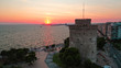 Aerial drone view of iconic historic landmark - old byzantine White Tower of Thessaloniki or Salonica at sunset with golden colours, North Greece