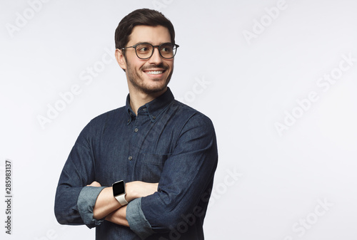Obraz Young handsome business man dressed in casual denim shirt with smartwatch on wrist, isolated on gray background - fototapety do salonu