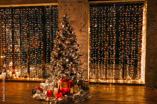 ciepły, przytulny magiczny wieczór w luksusowym starym salonie świątecznym bajkowa aranżacja wnętrz, okna pahoramic, choinka ozdobiona lampkami, prezentami, świecami, lampionami, oświetleniem girlandy. święta noworoczne