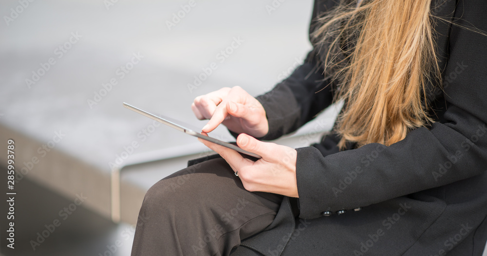 Detail of a businesswoman using her tablet while sitting on a bench in a city
