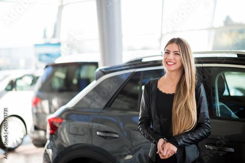 Fotomural Smiling woman choosing her car at a car dealer