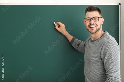 Fototapeta Male teacher writing on blackboard in classroom