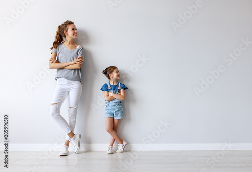 Photo sur Toile Pain happy family mother (big sister) and child daughter near an empty wall.