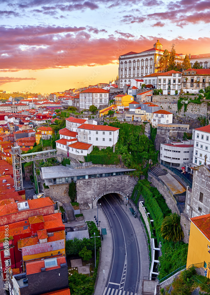 Fototapety, obrazy: Porto, Portugal. Top view aerial cityscape panorama of old town during beautiful evening sunset. Road street with tunnel under hill with houses with red roofs.