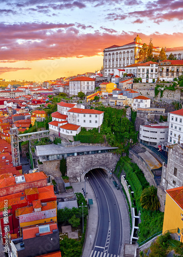fototapeta na szkło Porto, Portugal. Top view aerial cityscape panorama of old town during beautiful evening sunset. Road street with tunnel under hill with houses with red roofs.