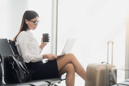Fototapeta Young woman with coffee working on laptop sitting in a departure lounge of airport obraz