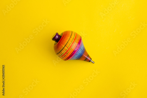 Fotomural  mexican toys, trompo from Wooden in Mexico on yellow background