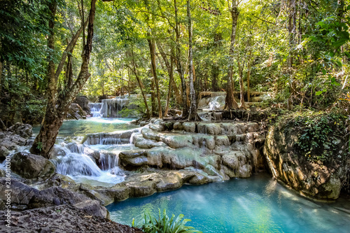 Wall Murals Forest river Smooth rocks with cascading water make a series of beautiful short waterfalls in the dense forest of Erawan National park in Thailand look staged