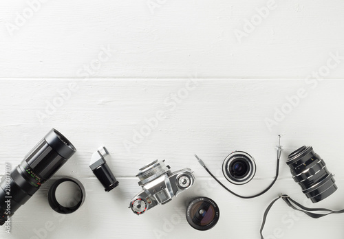 Obraz Retro analog film camera with lenses and photography equipment on white wooden background with copy space - photography or creativity concept, flat lay top view from above - fototapety do salonu