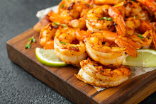 Grilled Shrimps Or Prawns Served With Lime, Garlic And White Sauce On A Dark Concrete Background. Seafood
