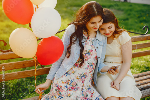 two young and bright girls spend their time in the summer park with balloons Wallpaper Mural