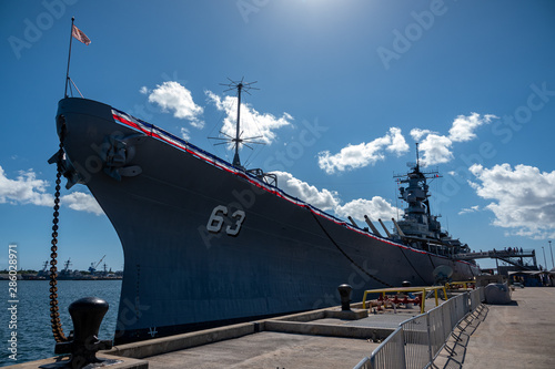 Battleship USS Missouri with sun, blue sky, and clouds at Pearl Harbor, Hawaii Wallpaper Mural