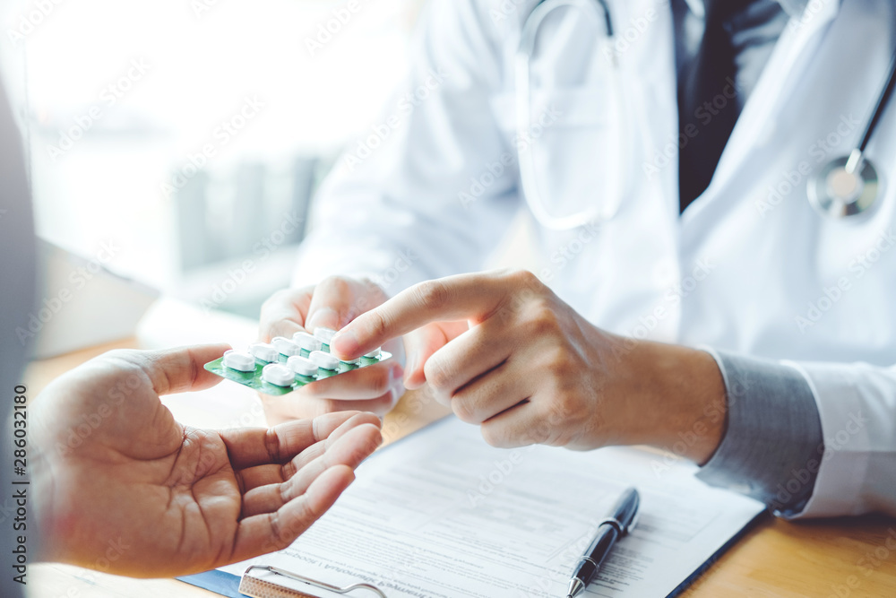 Fototapeta Doctor or physician recommend pills medical prescription to male Patient  hospital and medicine concept