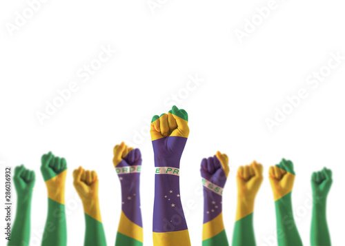Fotografia  Brazil flag on people hands with clenched fists raising up for labor day nationa
