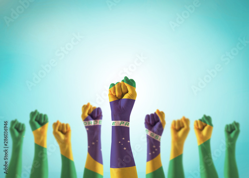 Fond de hotte en verre imprimé Brésil Brazil flag on people hands with clenched fists raising up for labor day national holiday celebration and stay strong for Brazilian power isolated on blue sky background (clipping path)