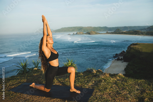 Fotografija Woman practicing yoga outdoors with amazing ocean and mountain view in morning