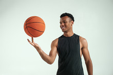 Best Player. Handsome Young African Man In Sport Clothing Spinning Basketball Ball On Finger And Smiling While Standing Against Grey Background