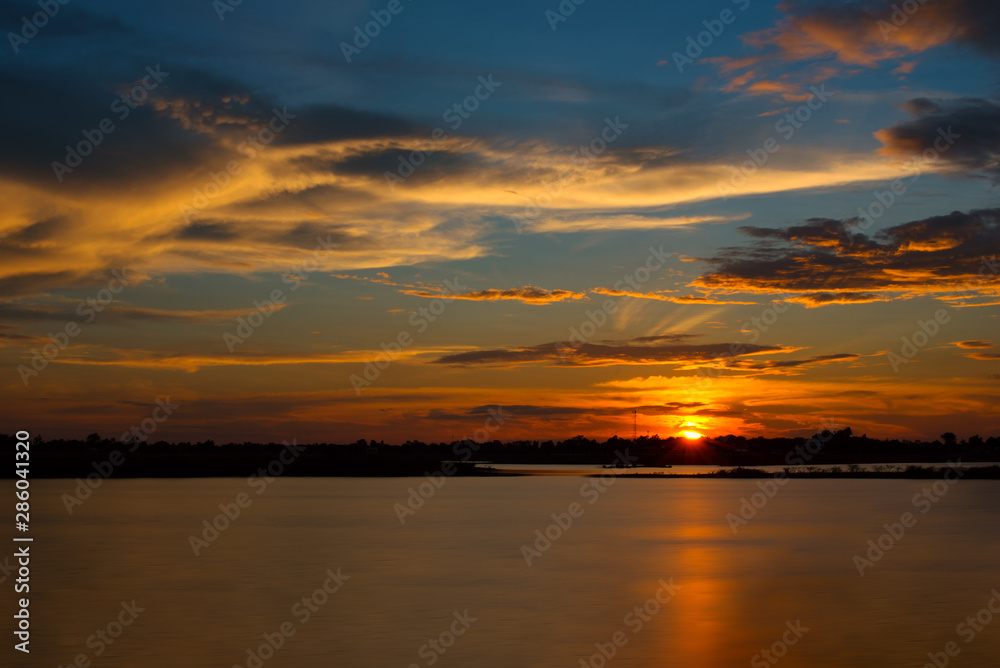 Beautiful Sunset in the sky with sky blue and orange light of the sun through the clouds in the sky, Orange and red dramatic colors over the lake. - Image