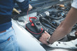 Mechanic with a multimeter testing car engine. Car service