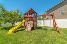 Wooden Playground Structure With Yellow Plastic Slide Swings And Climbing Wall