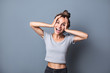 Portrait of an enthusiastic young woman screaming with joy over grey wall background.