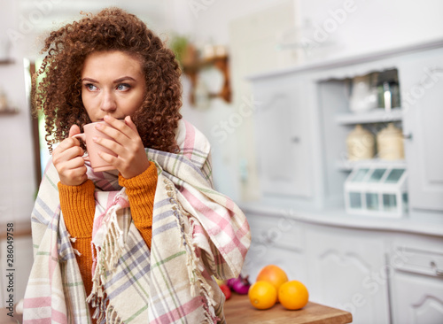 Obraz Young woman wrapped in blanket drinking hot tea - fototapety do salonu