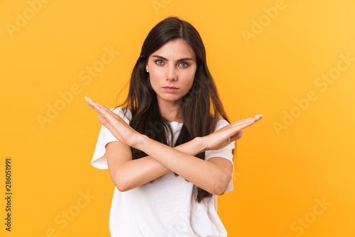 Image of confident woman 20s with dark hair frowning and doing rejection gesture Wallpaper Mural