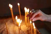 A Female Hand Lights A Candle ...