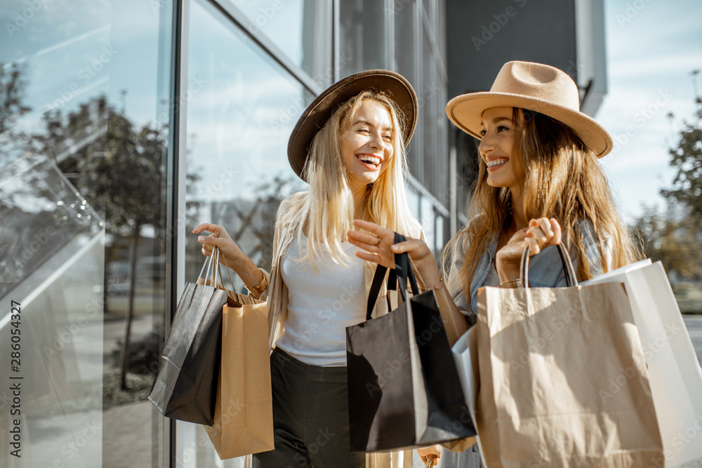 Fototapeta Two happy girlfriends looking on the shopwindow while standing with shopping bags near the mall