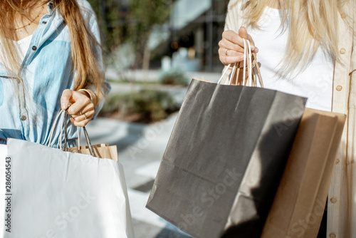 Photo  Women holding shopping bags outdoors while shopping, close-up view on the empty