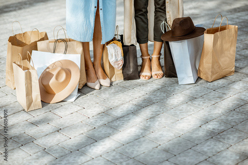 Fotografering Women stannding with shopping bags outdoors, close-up view on the women's legs a