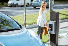 Businesswoman Plugging Charging Gun Into The Electric Gas Station On The Car Parking Outdoors