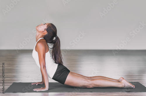 Cuadros en Lienzo  Asian woman stretching lower back with yoga cobra pose on exercise mat