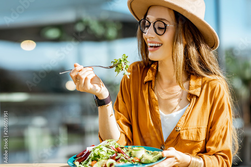 Stylish young woman eating healthy salad on a restaurant terrace, feeling happy Fototapeta