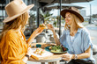 canvas print picture - Two female best friends eating healthy food while sitting together on a restaurant terrace on a summer day