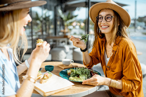 Recess Fitting Restaurant Two female best friends eating healthy food while sitting together on a restaurant terrace on a summer day