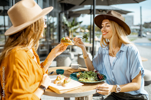 Fototapeta Two female best friends eating healthy food while sitting together on a restaurant terrace on a summer day obraz