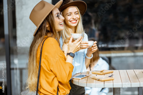 Obraz Two female best friends spending time together on the cafe terrace, feeling happy, enjoying coffee during a summer day - fototapety do salonu