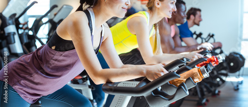 Poster Fitness Asian woman and her friends on fitness bike in gym