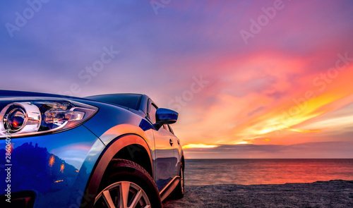 Stampa su Tela Blue compact SUV car with sport and modern design parked by beach at sunset