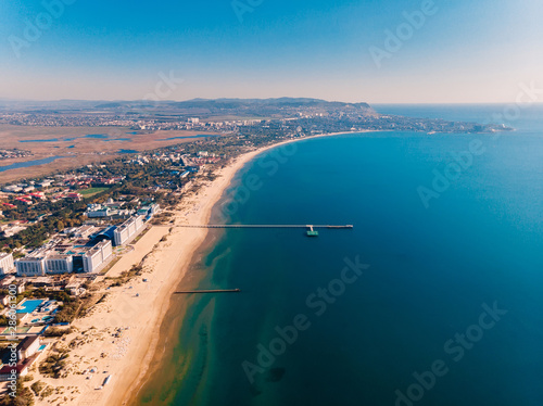 Aerial view of shore with pier, city and quit sea Wallpaper Mural