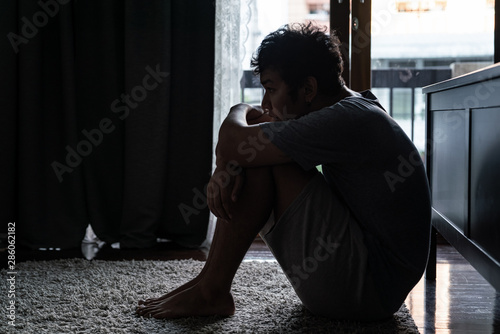 Obraz Wide shot of young adult asian loneliness sad man sitting on the floor in bedroom hugging the knees and cry. Broken heart despair man sitting on the floor and thinking alone. - fototapety do salonu