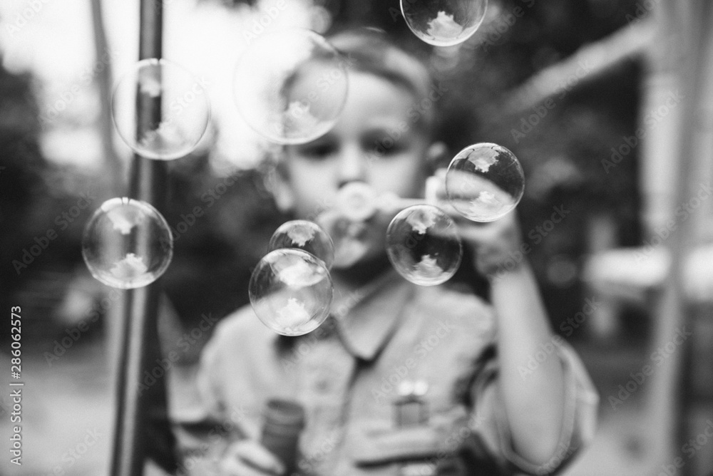 Fototapeta Little boy blowing bubbles. The concept of childhood.Black and white photo